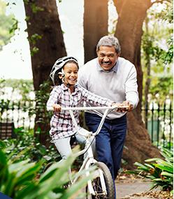 Mature man teaching child to ride a bike