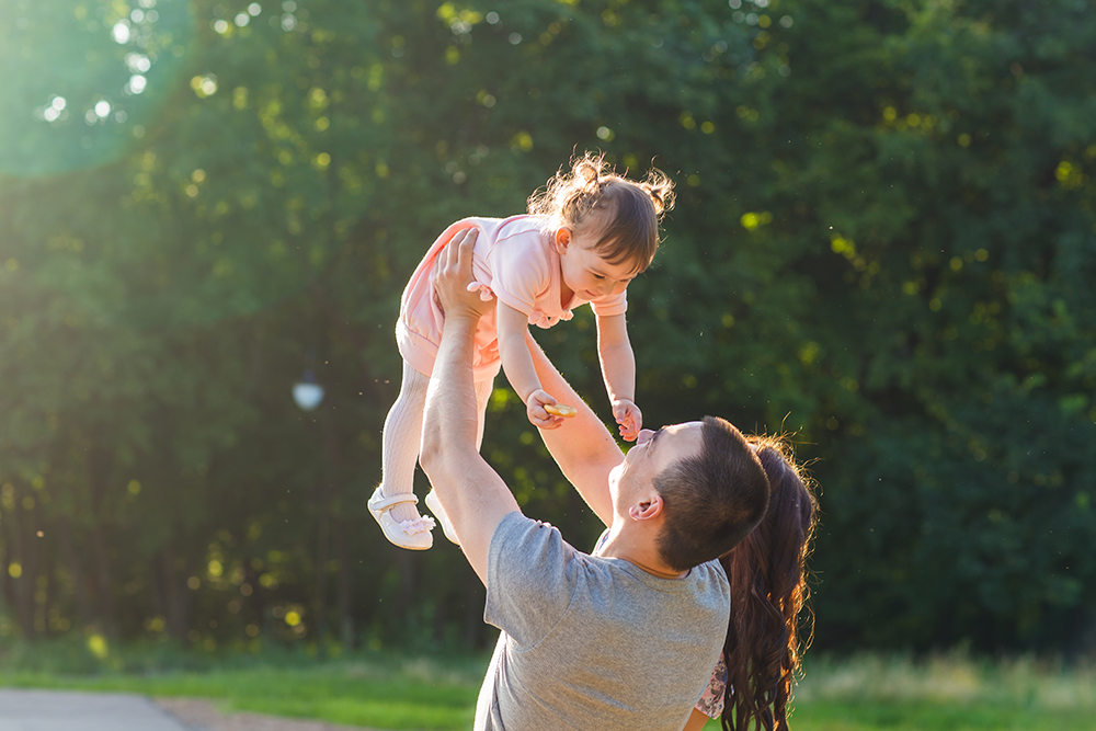 Man holding daughter in the air smiling