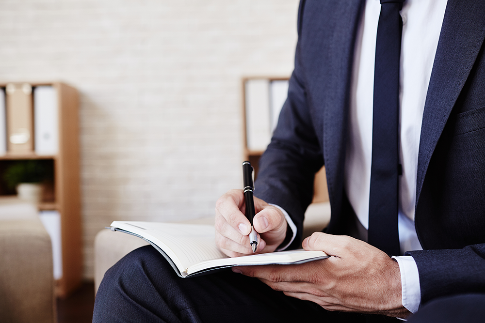 Man in suit writing will