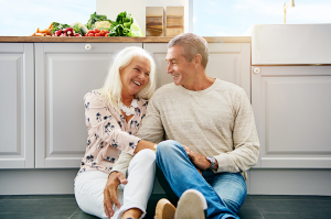 Mature couple sat on kitchen floor smiling at each other