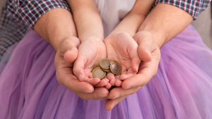 Adult hands cupping child hands with money in hands